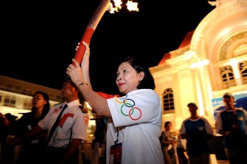 4月29日,奥运火炬手、胡志明市副市长阮氏秋霞手持火炬传递。当日,北京奥运圣火传递活动在越南胡志明市举行。  新华社记者周文杰摄