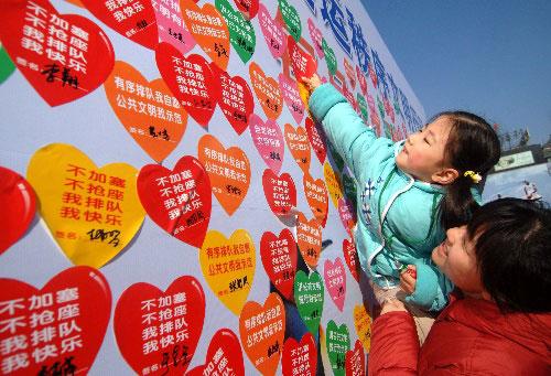 """2007年2月11日,一名小朋友在妈妈的帮助下在展板上贴下号召排队的小标签。当日,""""排队推动日""""活动启动仪式在北京王府井大街举行。北京市确定,每月11日为""""排队推动日"""",希望借此杜绝公共场所乱拥乱挤、城市交通乱行乱停等不文明行为,为奥运会创造文明有序的环境。(资料照片)新华社发"""