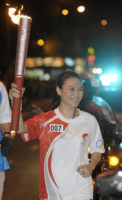 奥运火炬手潘美心手持火炬传递。新华社记者戚恒摄