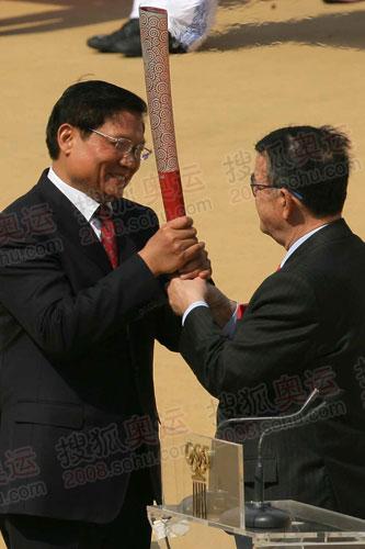 在交接仪式上,北京奥组委主席刘淇从希腊奥委会主席基里亚库手中接过奥运会圣火,并点燃了火种灯。