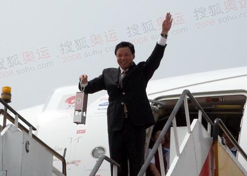 北京奥组委执行副主席手持火种灯走出舷梯