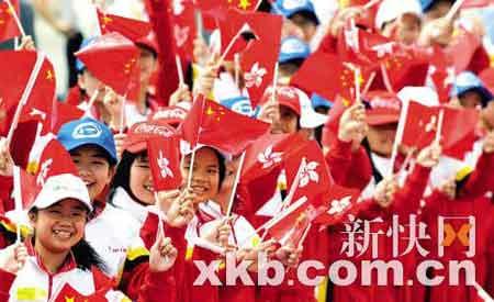 ■香港的小学生穿红衣手执国旗在沿路欢迎圣火到来。新华社发