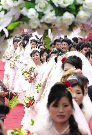 左图:新娘们在鲜花拱门外排队进入婚庆会场。