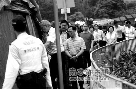 昨天,曾荫权在现场察看遇难者遗体时神情凝重。
