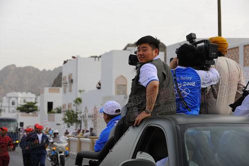 官网记者王非被迫站在小媒体车上拍摄(李东雷摄)
