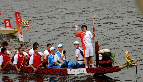 火炬手、香港游泳运动员施幸余乘坐龙舟进行传递。当日,北京奥运会圣火传递活动在中国香港举行。 新华社记者周文杰摄