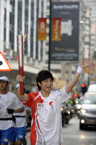 火炬手、香港艺人古巨基在进行传递。  新华社记者戚恒摄