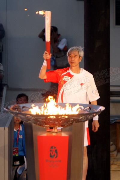最后一名火炬手梁庆庭点燃圣火盆