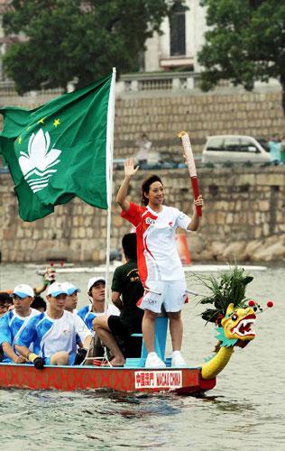 5月3日,奥运火炬手彭芷珊在龙舟上手持火炬传递。当日,北京奥运圣火传递活动在中国澳门举行。新华社记者周文杰摄