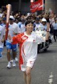 图文:奥运火炬手李丽青手持火炬传递