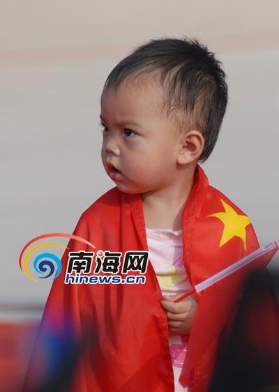 一名小孩围着国旗在凤凰岛观看圣火传递