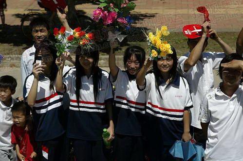 学生们挥舞着手中的花欢迎火炬