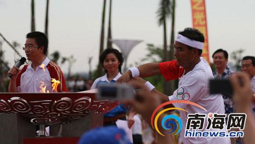 5月5日下午6时,全国道德模范姚义德在奥运圣火传递琼海站点燃圣火盆。本网记者李永金摄