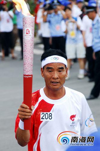 5月5日下午6时,全国道德模范姚义德高举奥运火炬,走进庆典现场。本网记者李永金摄