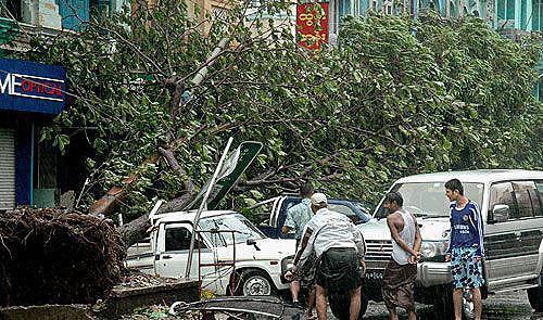 5月4日,在缅甸最大城市仰光街头,警察把被刮倒的树木搬走。(新华网)