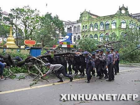 5月4日,在缅甸最大城市仰光街头,警察把被刮倒的树木搬走。新华社/法新