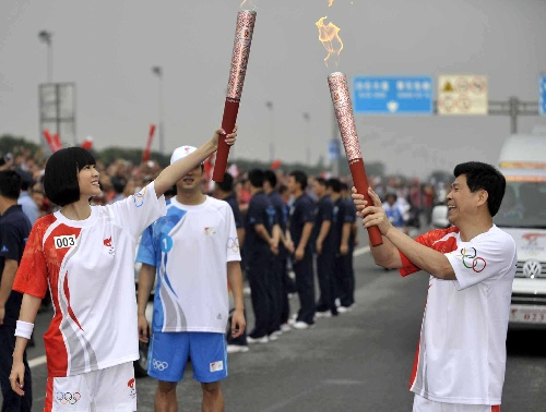 奥运火炬手刘江南(右)与李艾在传递过程中进行交接。当日,北京奥运圣火传递活动在广东省广州市举行。
