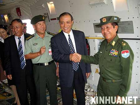 5月7日,在缅甸仰光国际机场,中国驻缅甸大使管木(右二)与接受中国政府捐赠物资的缅甸社会福利、救济和安置部部长貌貌瑞少将(右)握手。 新华社记者张云飞摄