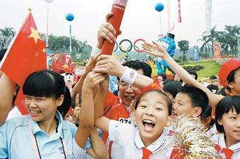 广州一名小姑娘摸到火炬后欣喜若狂。柯小军摄