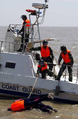 海警对跳海逃逸的嫌疑人采取救生措施。.