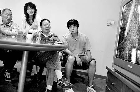 屈银华(左一)和王富洲(左三)今天上午在法制晚报社看圣火登珠峰电视转播 摄/记者吴海浪