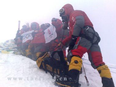 登山队员在峰顶展示中国国旗、奥运五环旗和北京奥运会会徽旗