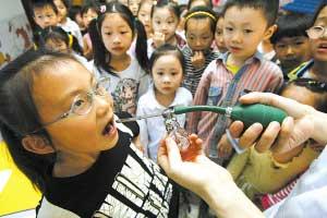 昨日,高新区启明幼儿园,医护人员正给孩子们口腔消毒 记者 钟志兵 摄