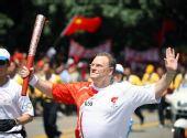 图文:奥运圣火在深圳传递 德克手持火炬传递