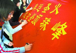 5月8日,体育馆地区团员青年志愿者制作宣传栏,写下祝福语,热烈祝贺北京奥运火炬接力珠峰传递顺利登顶成功。记者 戴冰摄