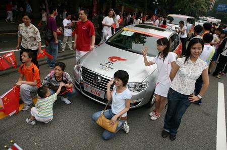能够和为奥运圣火保驾护航的大众汽车拍张合影成为很多市民重要的欢庆活动之一