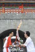 图文:奥运圣火在惠州传递 两名火炬手交接
