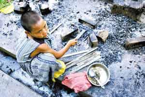 在缅甸仰光的一块空地上,一名受灾的男孩正准备生火做饭。