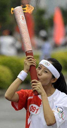 奥运火炬手张洁在传递过程中亲吻火炬 新华社记者刘大伟摄