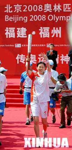 第一棒火炬手郑美珠手持火炬开始传递