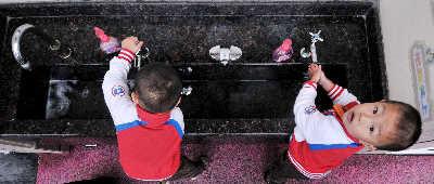 5月9日,上海一家托儿所的小朋友在进校门前洗手。早报记者 鲁海涛 实习生 曹磊图