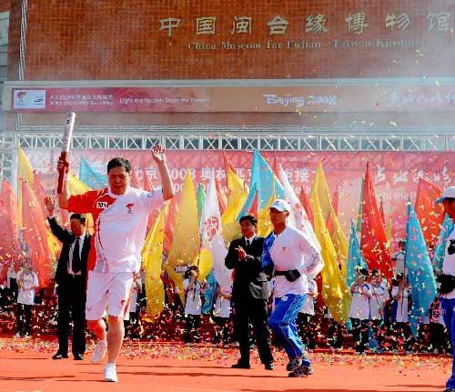 5月12日,火炬手王家声在进行传递。当日,北京奥运圣火传递活动在福建省泉州市和厦门市两地举行。新华社记者张国俊摄