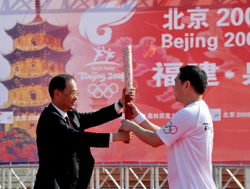 泉州市委书记徐钢(左)在起跑仪式上,将点燃的火炬交给第一棒火炬手王家声。当日,北京奥运会圣火在福建省泉州市传递。新华社记者张国俊摄