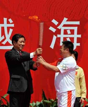 5月12日,在起跑仪式上,厦门市委书记何立峰(左)将火炬交给火炬手郭跃华。当日,北京奥运会圣火在福建省厦门市传递。新华社记者张国俊摄