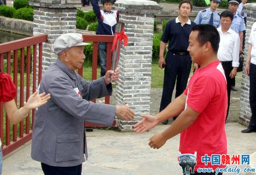 图为老红军火炬手刘家祁在瑞金沙洲坝红井旧址与另一名火炬手进行交接。