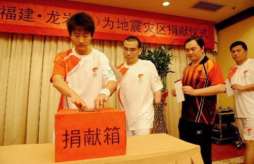月13日,火炬手和工作人员在捐献仪式上捐款。当日,北京奥运会火炬传递福建龙岩站举行捐献仪式,为地震灾区献爱心。 新华社记者张国俊摄