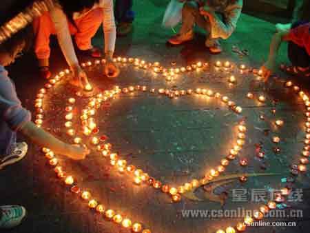 """5月14日晚,长沙步行街中心广场,长沙网友聚集这里为地震灾区人民点灯祈祷,""""我们在一起,我们是一家人,为支援灾区捐钱献血,点灯祈祷,吹响了爱心集结号!""""(摄影 刘莉)"""