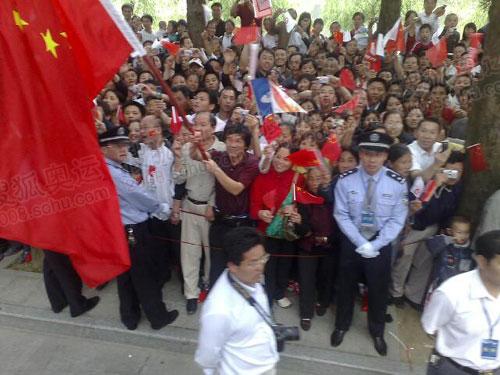 沿途群众高举国旗迎接火炬