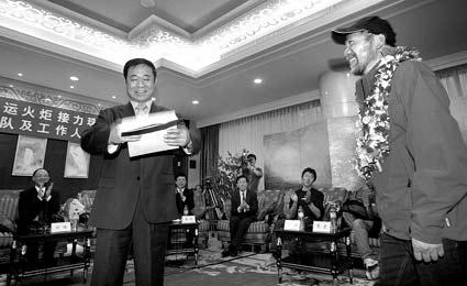 王勇峰(右)把装着善款的信封交给领导 摄/记者杨威