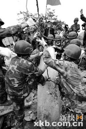 昨日上午,消防战士在什邡市蓥华镇废墟中锯开钢筋,进行营救。新华社图片