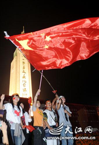 八一起义纪念踏下挥舞着国旗(大江网记者 喻云亮 摄)