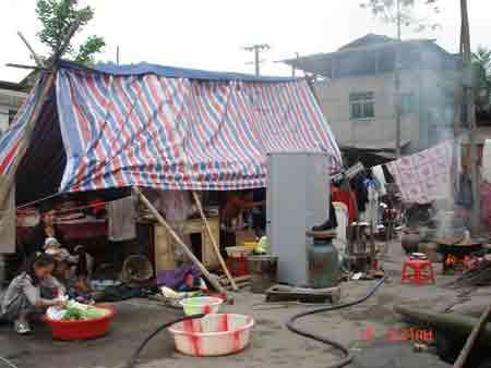 八角镇杉木林村10组陈维全一家六口一人重伤,留在家的人员积极自救,图为正在废墟上搭建的临时帐篷上洗衣做饭