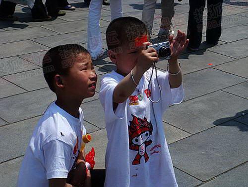 身着奥运表示服装的小朋友也想拍圣火.