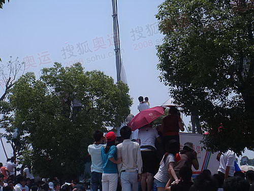 为了能在庆典现场看到火炬,很多市民爬树,登在车上