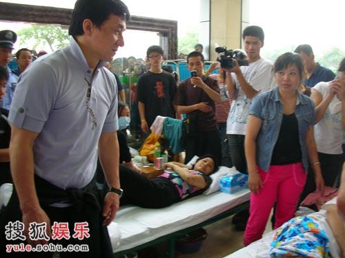 成龙来到一位受伤的孩子面前,轻生安慰她