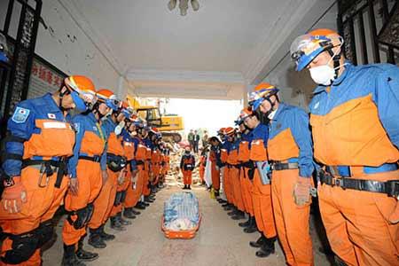 5月17日,日本搜救人员向遇难者遗体默哀。当日7时25分,日本救援人员历经16个小时的搜救,在四川青川县乔庄镇一处倒塌的六层楼房废墟中挖出两具遇难者遗体。 新华社记者 李涛摄
